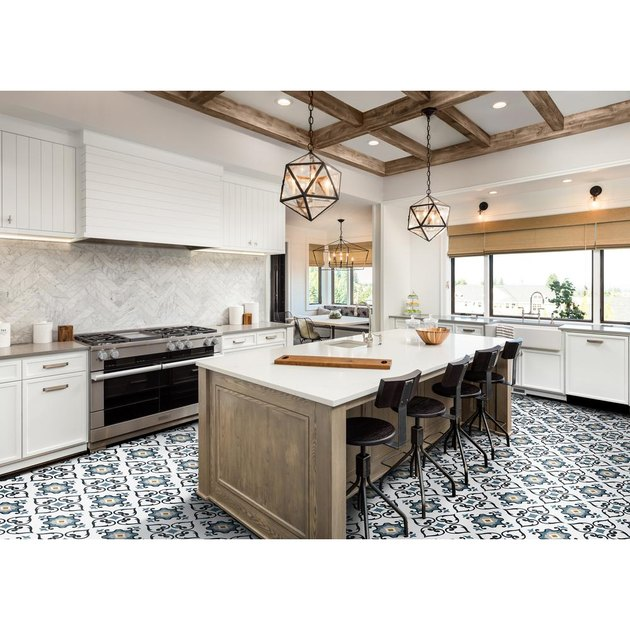 Vinyl patterned tile flooring in contemporary kitchen with white cabinetry and island with black barstools