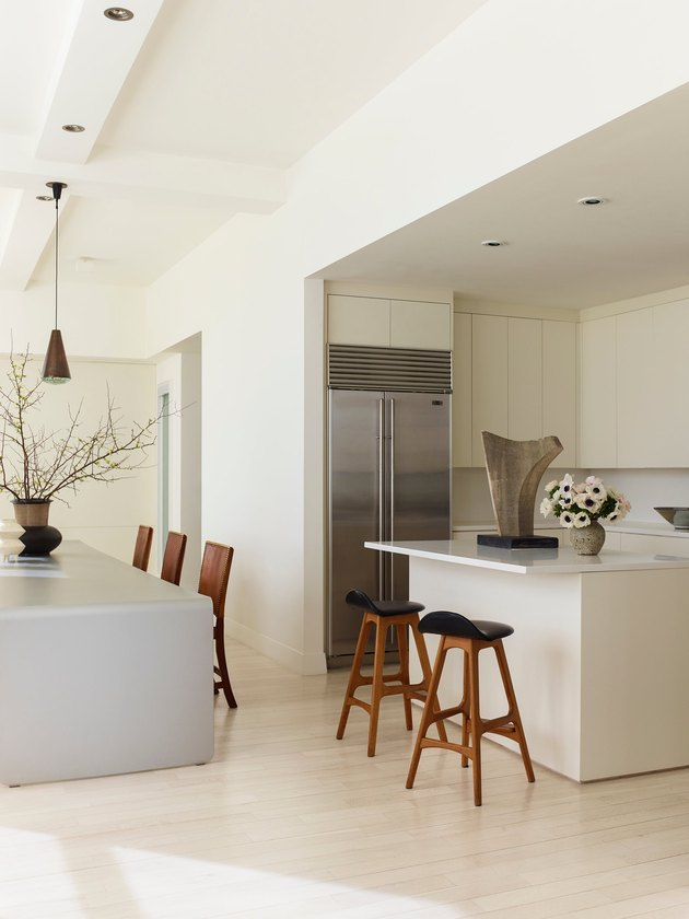 Modern kitchen with pale wood floors and cabinetry and high ceilings with recessed lighting and pendant light over table