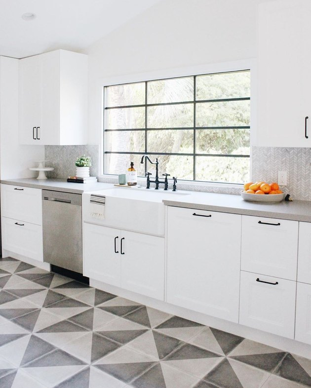 Small gray and white tile herringbone backsplash in modern white kitchen