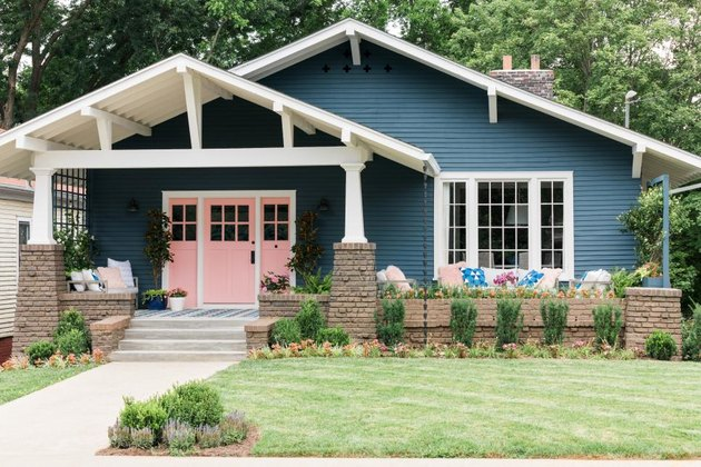 pink Craftsman-style door paired with blue exterior siding