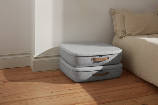 bedroom space with two gray felt storage boxes