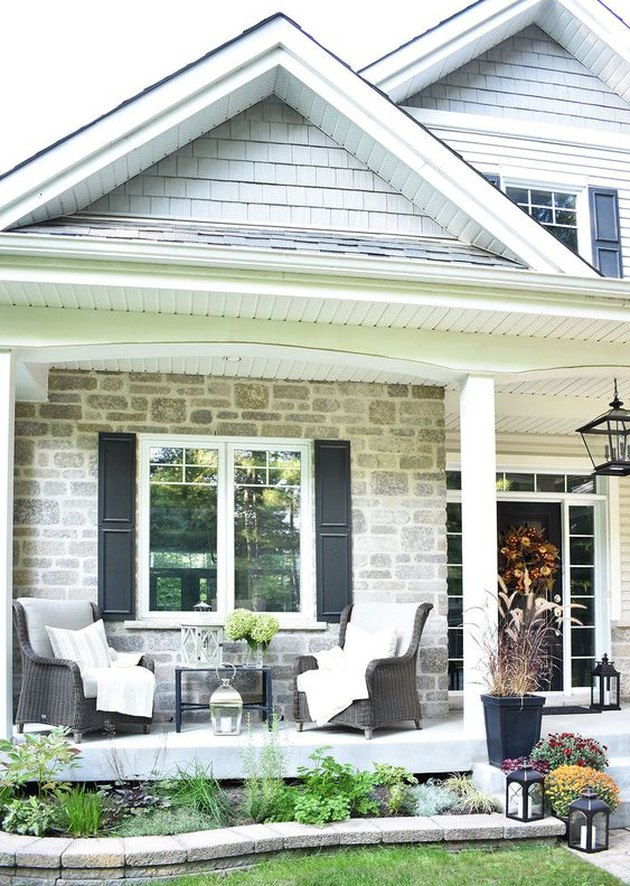 Craftsman front porch with brick exterior and wicker furniture