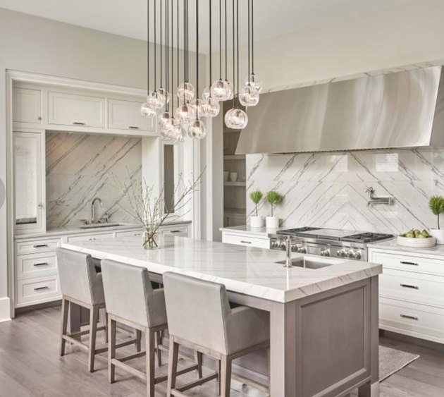Gray kitchen island with matching gray bar stoops and marble counters. Contemporary chandelier.