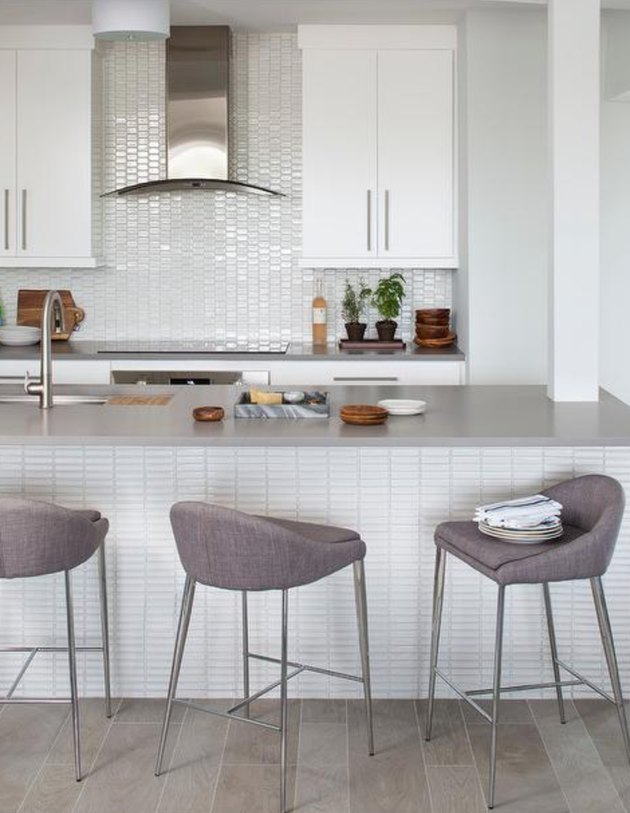 Kitchen with white tile backsplash, white cabinets and gray countertop.