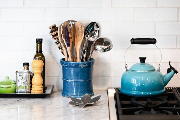focus on countertop with blue kettle, cooking equipment, spices