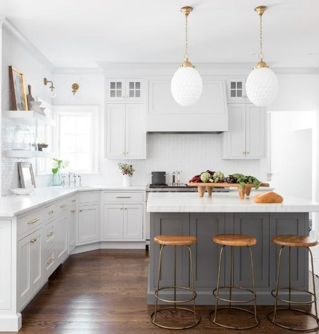 Kitchen with white cabinets and counter tops, hardwood floors, gray kitchen island and white pendant lamps.