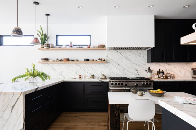 large kitchen with marble countertop and white walls