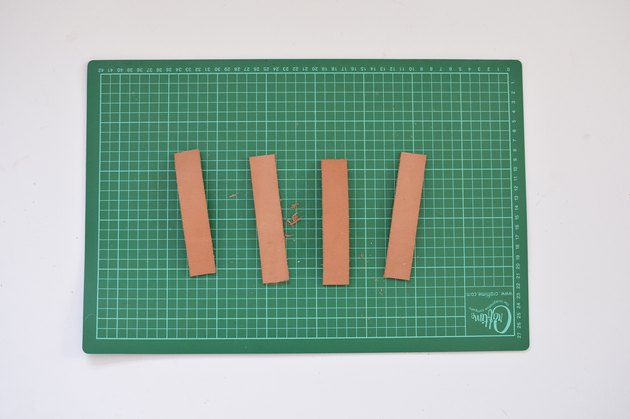 Green cutting mate with 4 identical strips of leather.