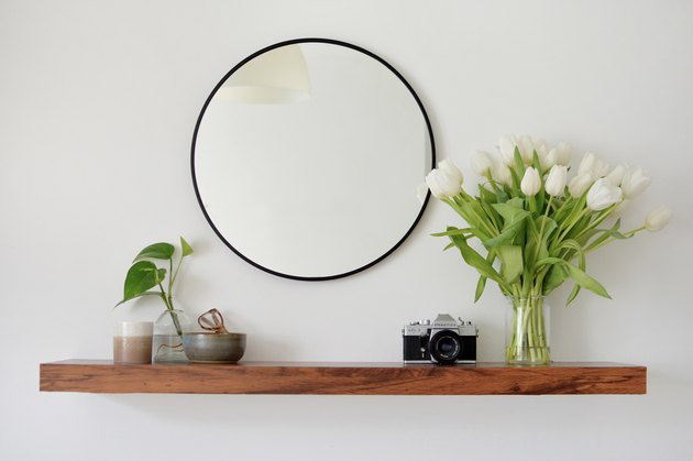 walnut floating shelf vase of white flowers, catch all bowl and wall mirror,