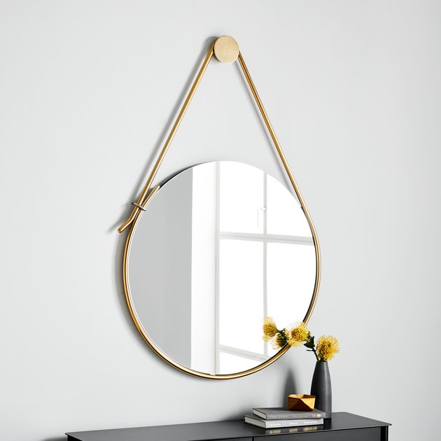 circular mirror hanging from a strap