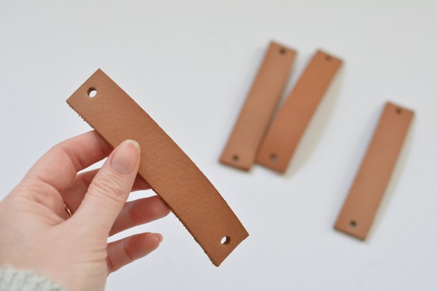 Hand holding piece of tan leather with a hole punched at each end.
