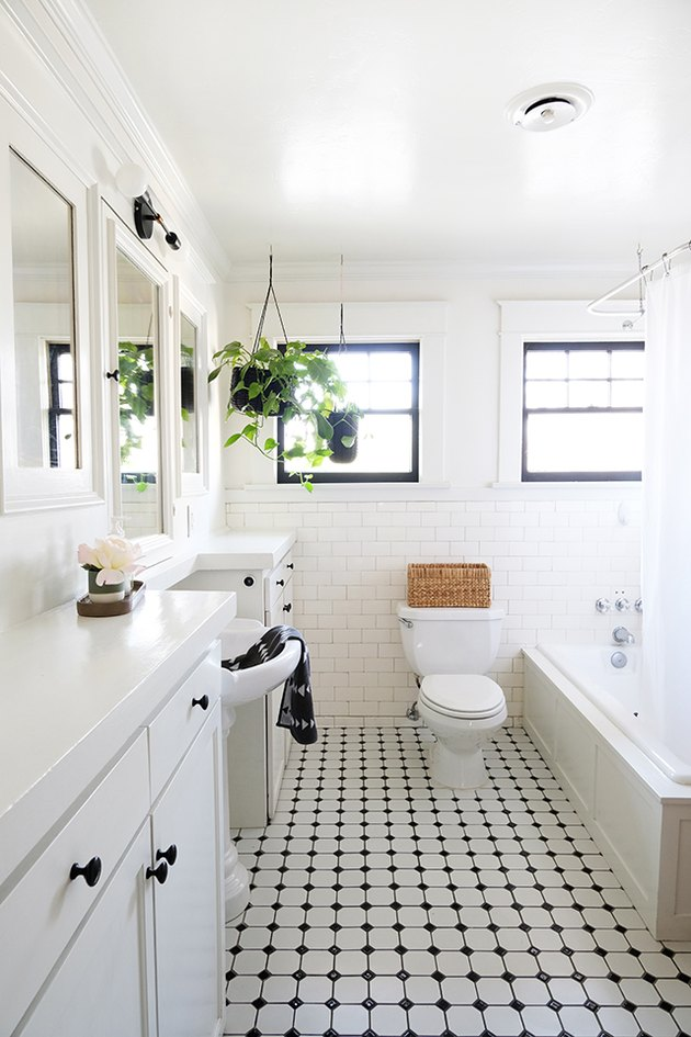 white bathroom with tub/shower combo, white bathroom sink and vanity and black and white checkered floor tiles