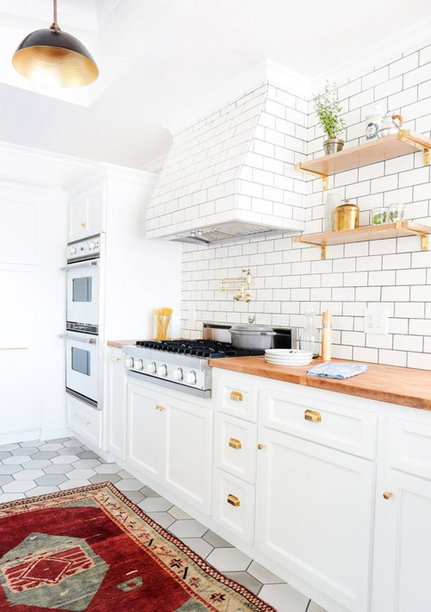 white kitchen cabinet idea with white subway tile and area rug