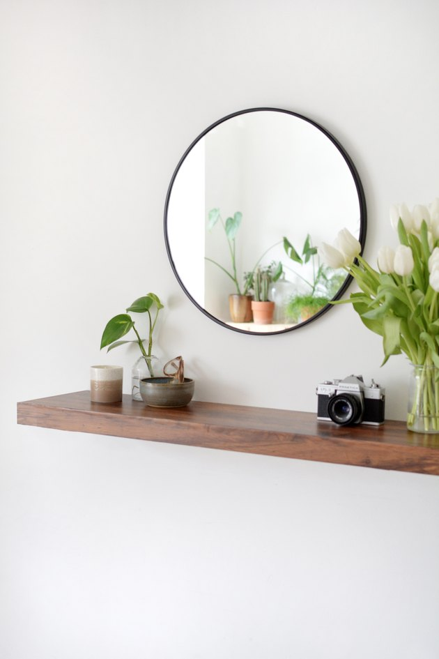 walnut floating shelf vase, white flowers, catch all bowl and circular wall mirror,