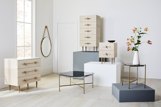 minimalist room displaying dressers, tables, and a mirror