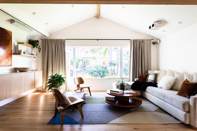 living room with arched ceiling, blue-and-white rug, floating credenza, long taupe couch