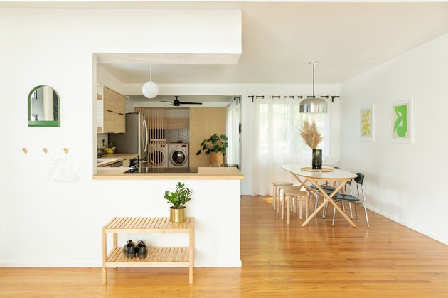 open living area with kitchen, breakfast bar, table, white walls, wood floors