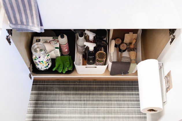 under the sink cabinet featuring organized boxes of cleaning supplies
