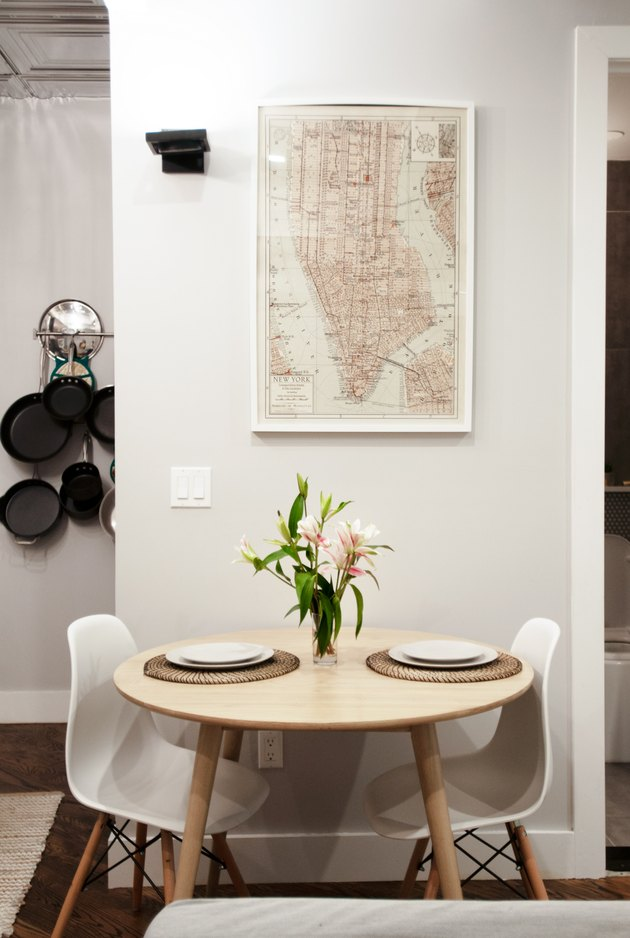 dining table near wall with framed map