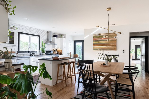 open living and dining room with island, plants, wood table, modern pendant light
