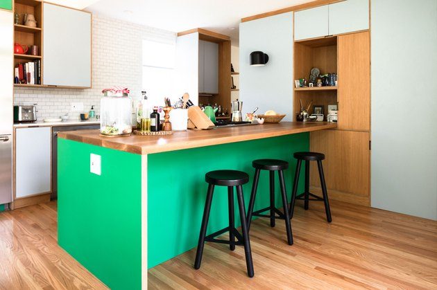 green kitchen island surrounded by mint cabinetry and wood floors and white subway tile walls