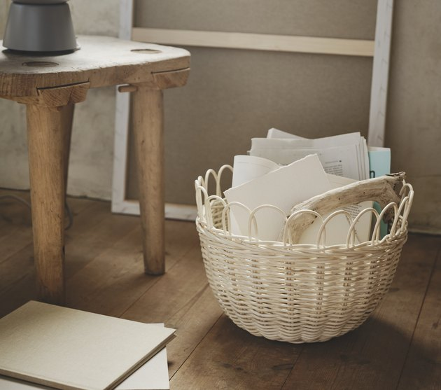 woven basket with papers on hardwood floor
