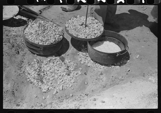 biscuits being made in a Dutch oven over coals with a coal-covered lid being placed on top