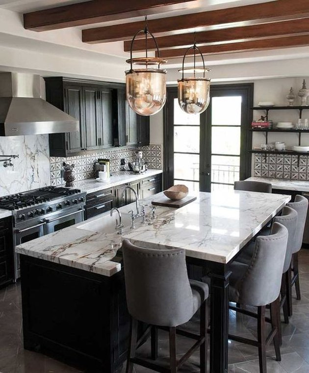two tier kitchen island with black base and marble countertops and glass pendant lights