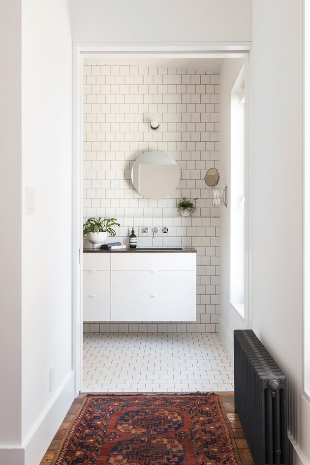 Floating White Bathroom Cabinet with subway tile wall and floor  by Elizabeth Roberts Architecture