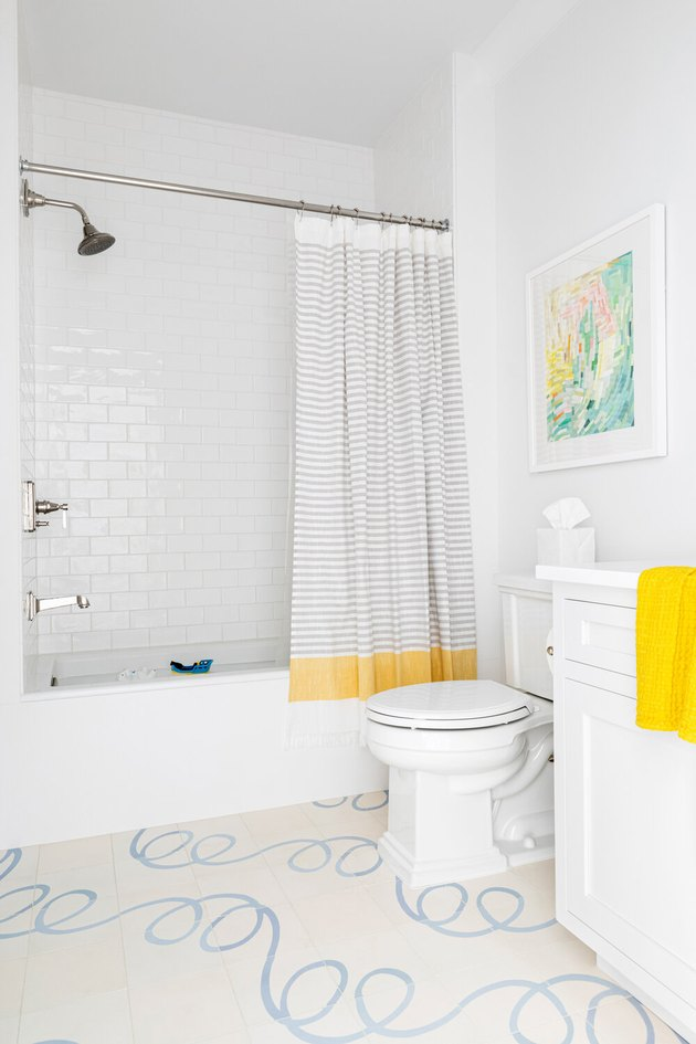 White Bathroom Cabinet with patterned flooring and white subway tile shower by Chango & Co.