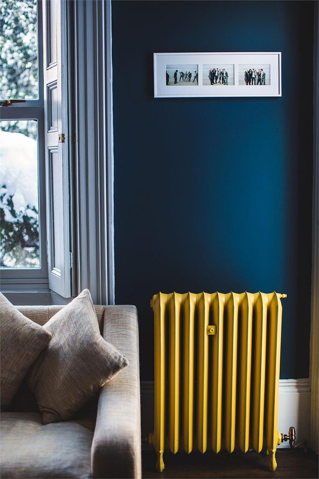 living room with yellow radiator and dark blue walls