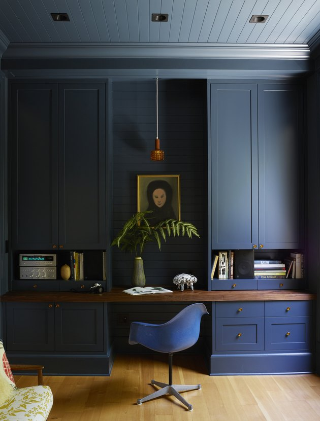 Office with dark blue cabinetry, Eames chair and wood ceiling in blue