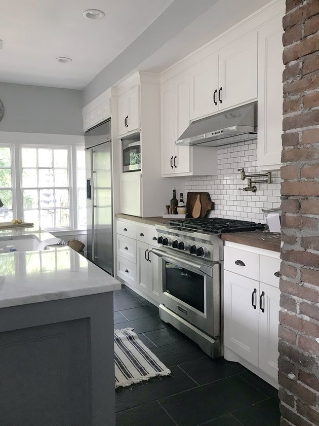 Black kitchen floor in traditional kitchen with white subway tile and brick