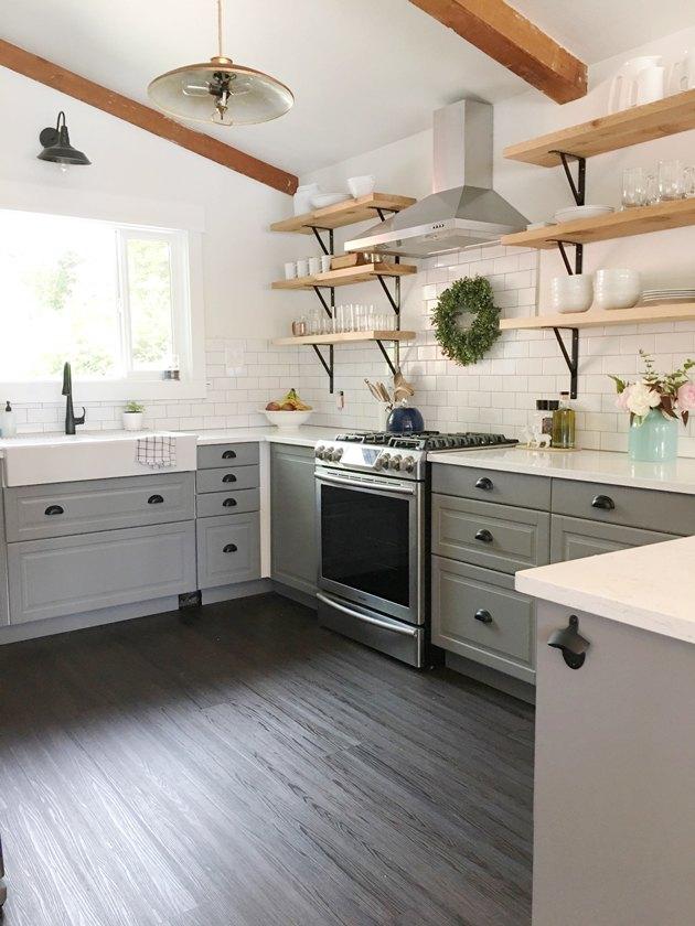 Black kitchen floor in farmhouse kitchen with white subway tile and open shelves