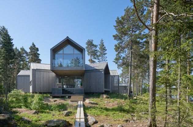 Scandinavian style house in gray color with large window in natural landscape with trees