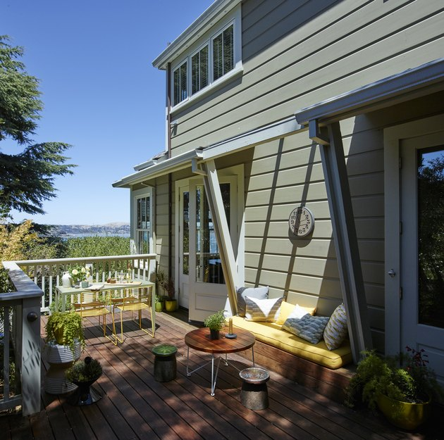 Sausalito farmhouse in green with wood deck and outdoor seating