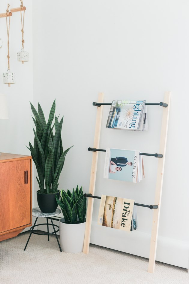 DIY ladder shelving with magazines hanging from each rung for small space