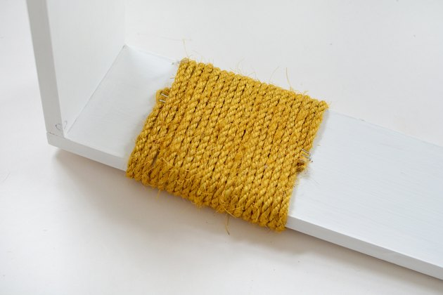 Yellow sisal rope wrapped around white wood