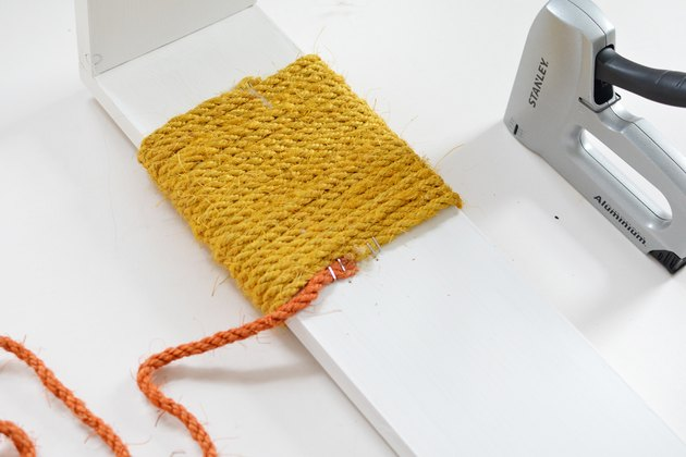 Yellow and orange sisal rope wrapped around white wood