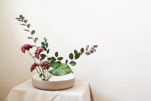diy ikebana flower arrangement of burgundy flowers and long green leaves