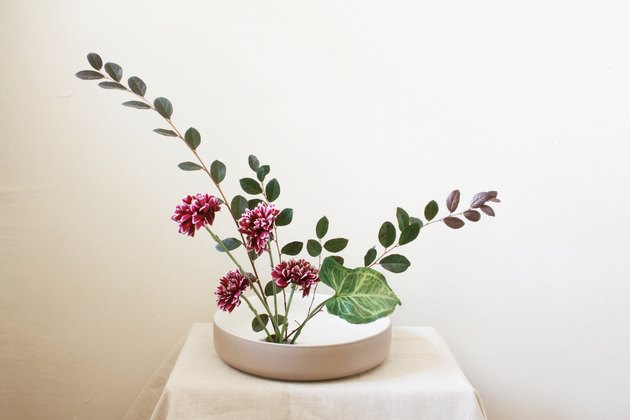 large green leaf inserted into ikebana flower arrangement