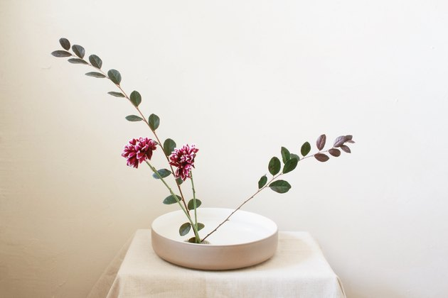 burgundy flowers and two long leaf stems inserted into flower frog inside shallow bowl