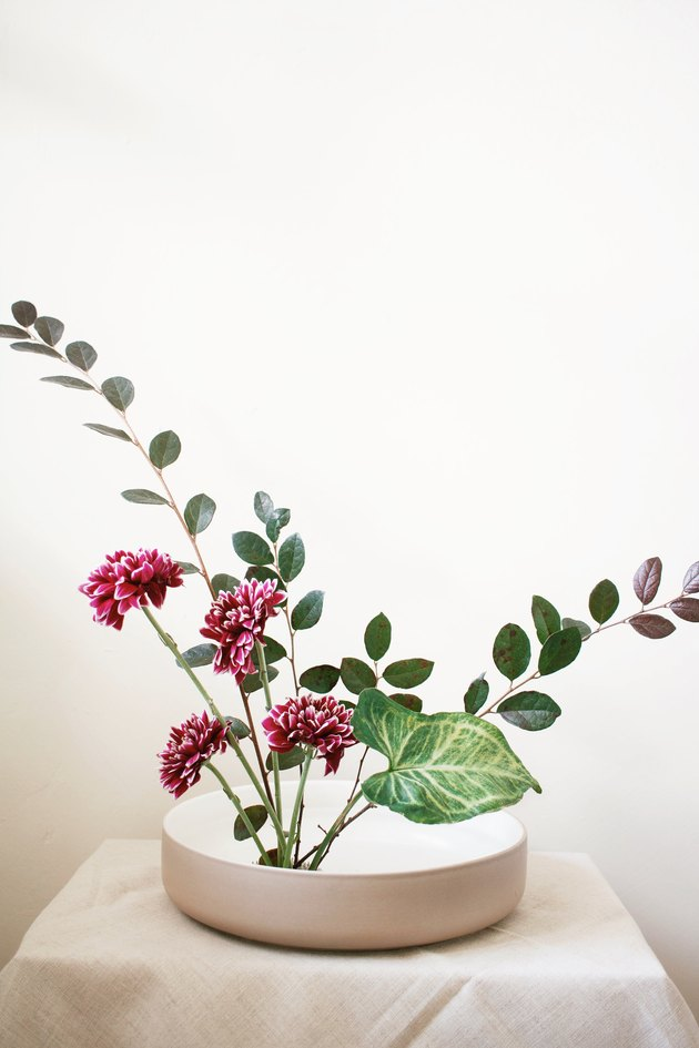 Arrangement diy ikebana avec fleurs bordeaux et feuilles vertes