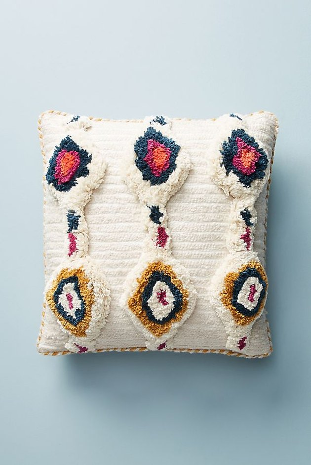 Tufted cream throw pillow with blue, red, and yellow abstract diamonds