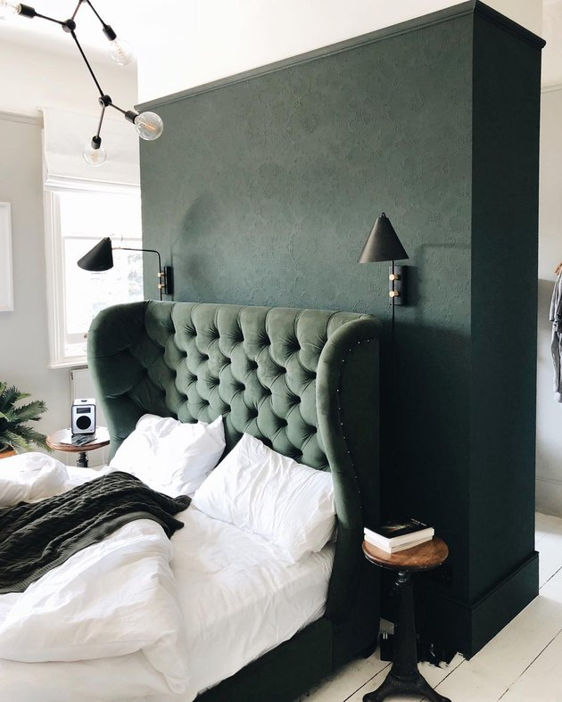 green tone-on-tone bedroom with tufted wingback headboard