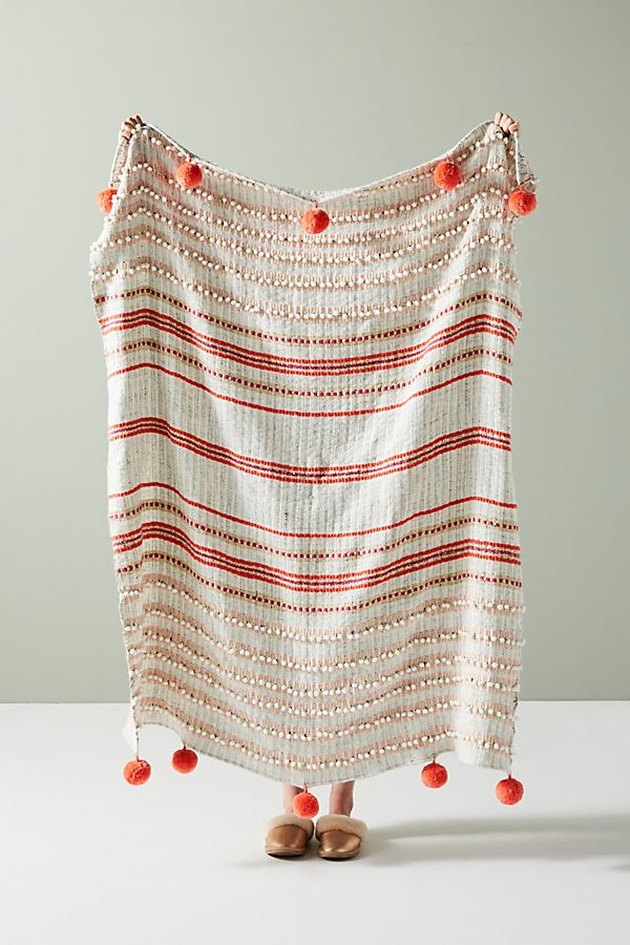 Beige throw blanket with red-orange stripes and pom poms