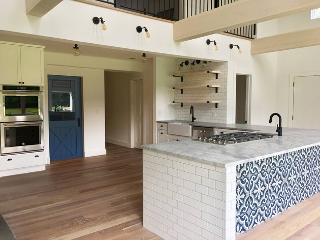 Kitchen island back panel idea with patterned tile by Dichotomy Interiors
