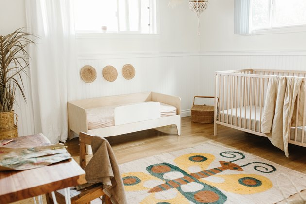 Scandinavian nursery idea with crib and toddler bed in light wood finish with vintage rug
