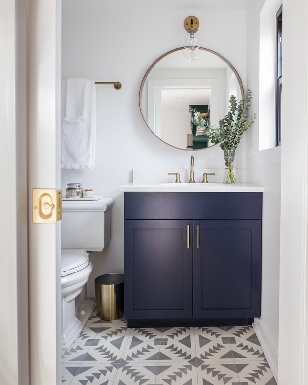 navy blue bathroom cabinets in boho bathroom with patterned tile and white countertop