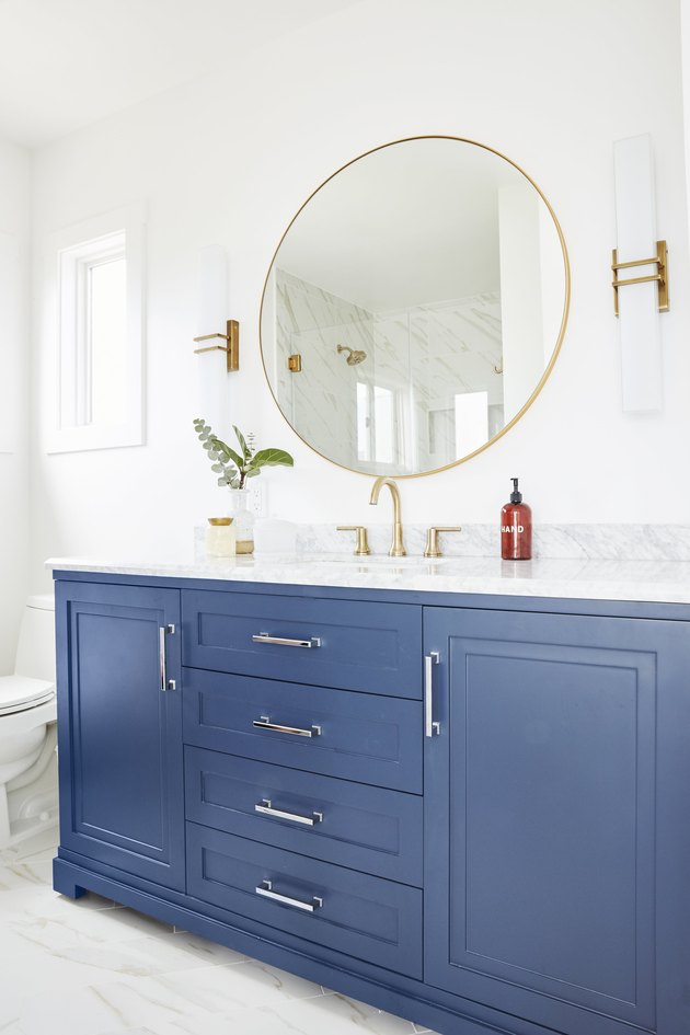 glamorous blue bathroom cabinets with white countertop and brass fixtures